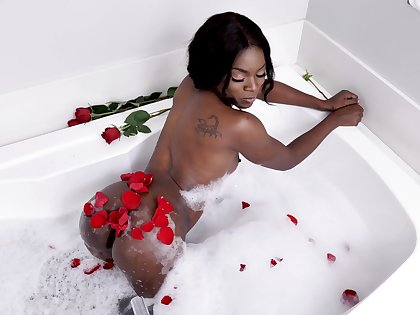 Ebony beauty reveals her curvy ass and tits in seductive tub scenes